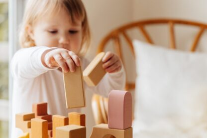 little girl playing with wooden blocks at home