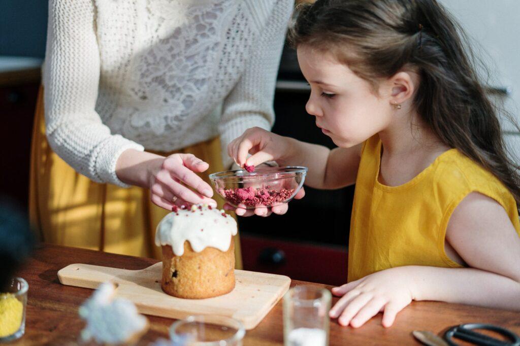 girl in yellow shirt holding brown cake