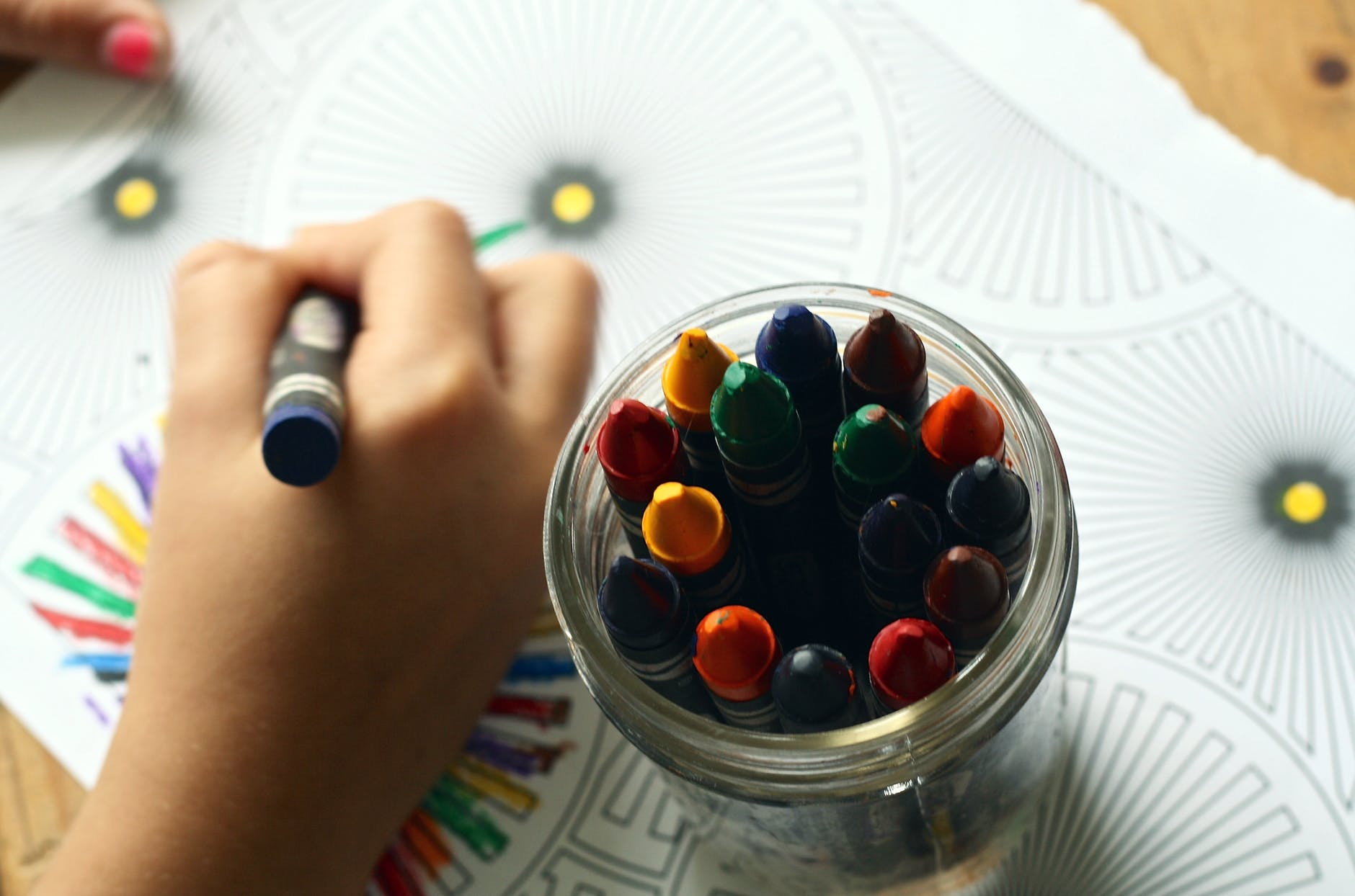 person coloring art with crayons