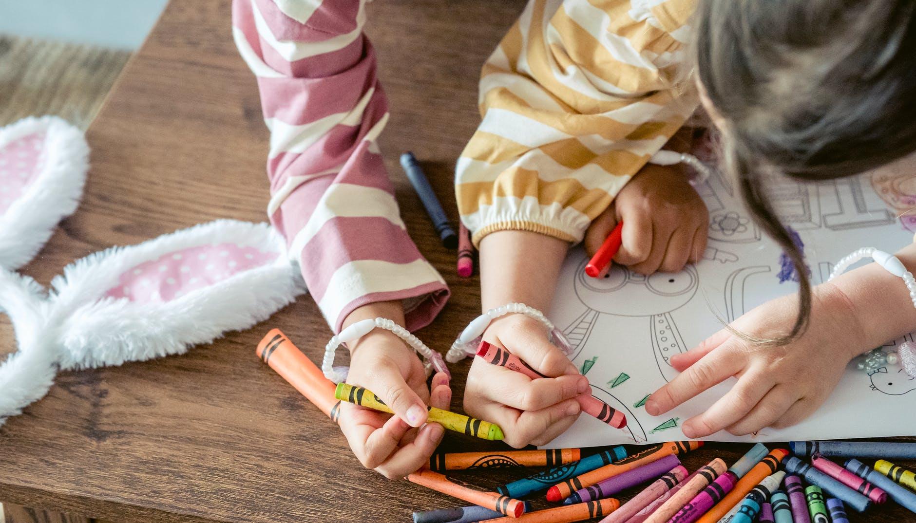 girls coloring sun on paper for easter celebration